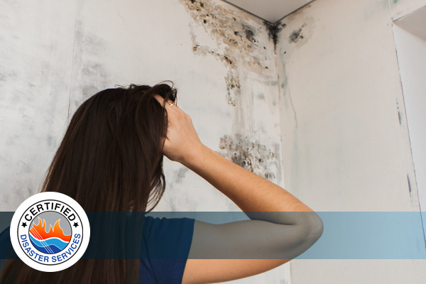 A woman scratching her head while staring at a mold-infested corner of her home's ceiling